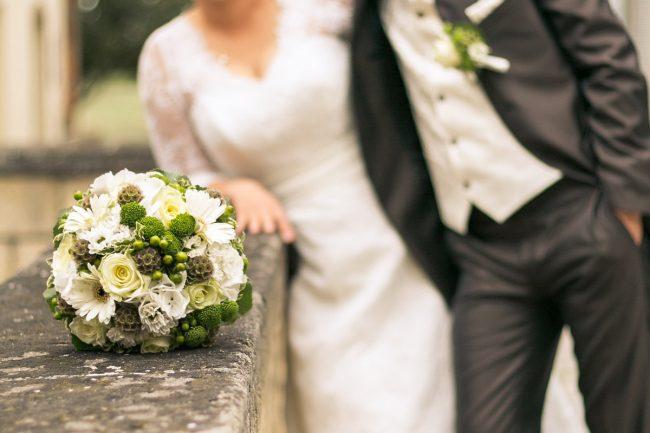 Brautstrauss liegt auf der Brueckenmauer und das Brautpaar lehnt dahinter