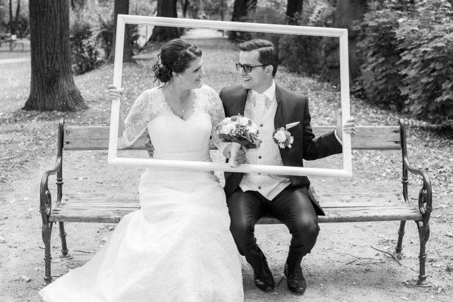 Hochzeitspaar sitzend auf einer Bank, fotografiert durch einen Rahmen von Martin Thüringer