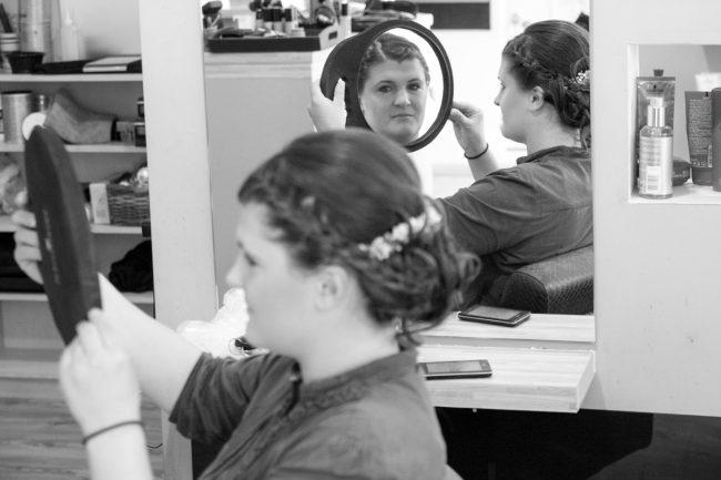Braut kontrolliert mit Spiegel die Haare beim Hochzeitsfrisoer in Laa