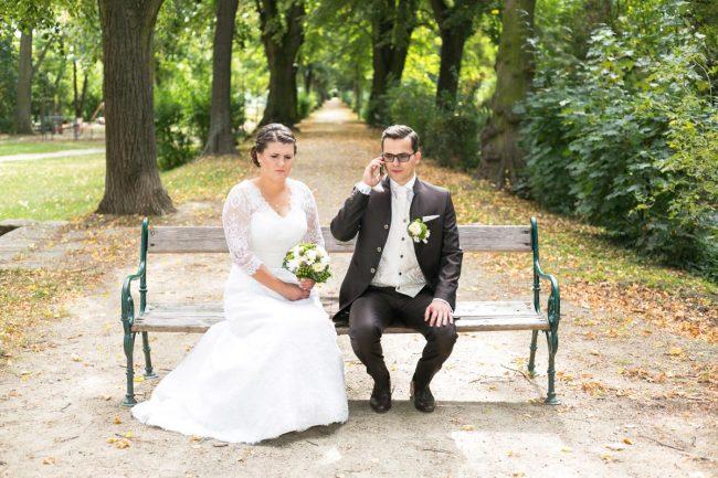 Hochzeitspaar sitzend auf Parkbank und der Braeutigam telefoniert